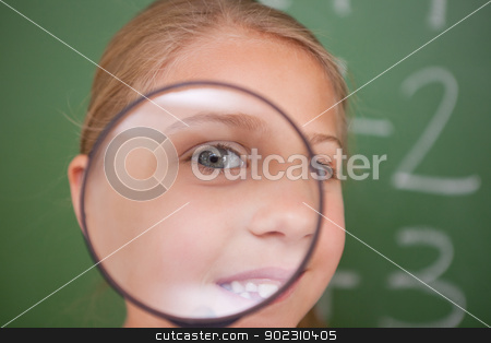 Close up of a schoolgirl looking through a magnifying glass stock photo, Close up of a schoolgirl looking through a magnifying glass in a classroom by Wavebreak Media