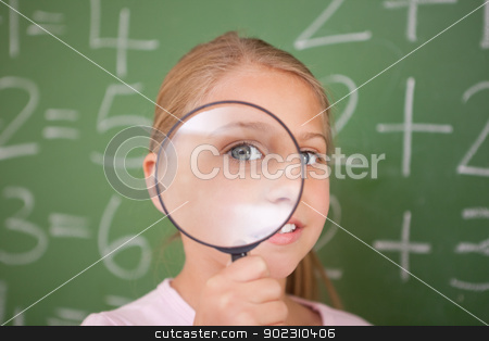 Cute schoolgirl looking through a magnifying glass stock photo, Cute schoolgirl looking through a magnifying glass in a classroom by Wavebreak Media