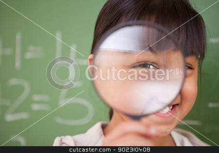 Close up of a cute schoolgirl looking through a magnifying glass stock photo, Close up of a cute schoolgirl looking through a magnifying glass in a classroom by Wavebreak Media