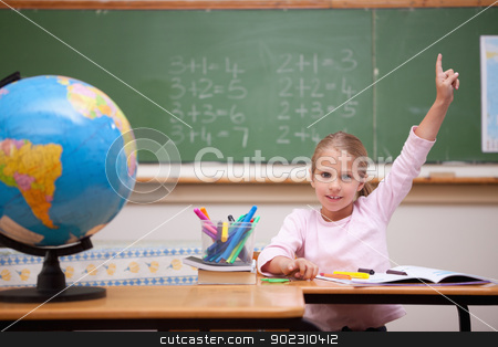 Cute schoolgirl raising her hand to answer a question stock photo, Cute schoolgirl raising her hand to answer a question in a classroom by Wavebreak Media