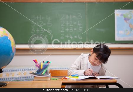 Schoolgirl drawing on a coloring book stock photo, Schoolgirl drawing on a coloring book in a classrooom by Wavebreak Media