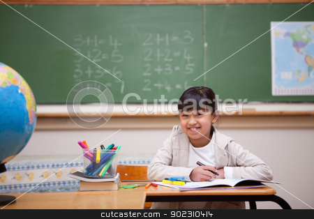 Smiling schoolgirl drawing on a coloring book stock photo, Smiling schoolgirl drawing on a coloring book in a classroom by Wavebreak Media