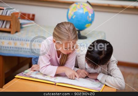 Schoolgirls reading a fairy tale stock photo, Schoolgirls reading a fairy tale in a classroom by Wavebreak Media