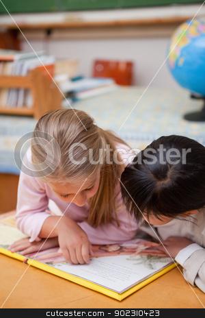 Portrait of focused schoolgirls reading a fairy tale stock photo, Portrait of focused schoolgirls reading a fairy tale in a classroom by Wavebreak Media