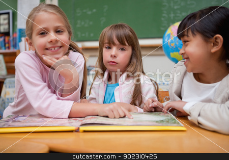 Schoolgirls reading a fairy tale to their classmate stock photo, Schoolgirls reading a fairy tale to their classmate in a classroom by Wavebreak Media
