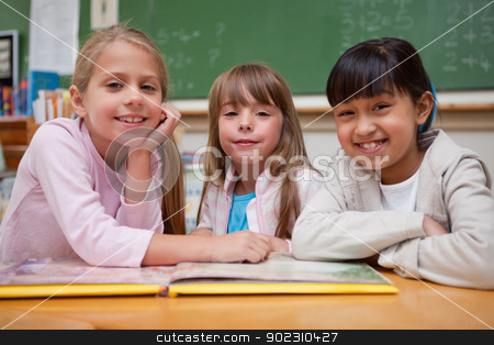 Smiling schoolgirls reading a fairy tale to their classmate stock photo, Smiling schoolgirls reading a fairy tale to their classmate while looking at the camera by Wavebreak Media