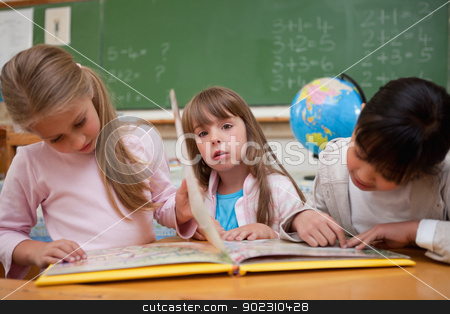 Cute schoolgirls reading a fairy tale to their classmate stock photo, Cute schoolgirls reading a fairy tale to their classmate in a classroom by Wavebreak Media