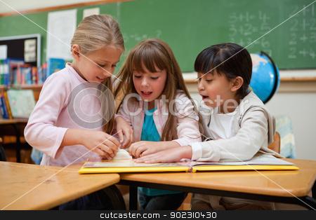 Little schoolgirls reading a fairy tale stock photo, Little schoolgirls reading a fairy tale in a classroom by Wavebreak Media