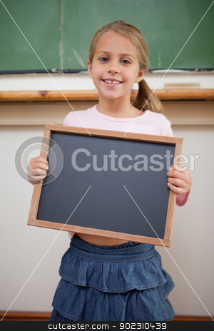 Portrait of a happy girl holding at a school slate stock photo, Portrait of a happy girl holding at a school slate in a classroom by Wavebreak Media
