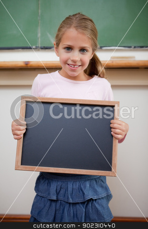 Portrait of a young girl holding at a school slate stock photo, Portrait of a young girl holding at a school slate in a classroom by Wavebreak Media