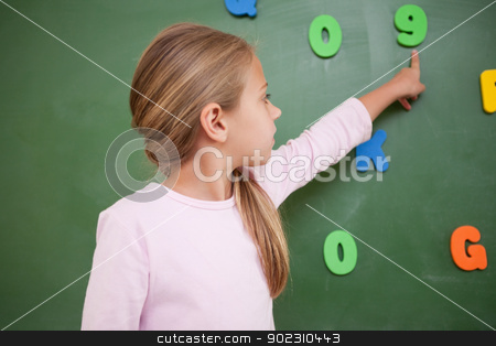 Schoolgirl pointing at a number stock photo, Schoolgirl pointing at a number on a blackboard by Wavebreak Media