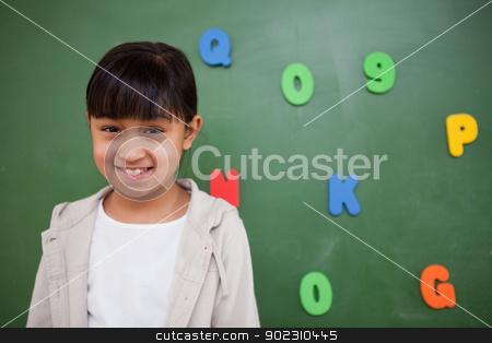 Smiling schoolgirl posing in front of a blackboard stock photo, Smiling schoolgirl posing in front of a blackboard in a classroom by Wavebreak Media