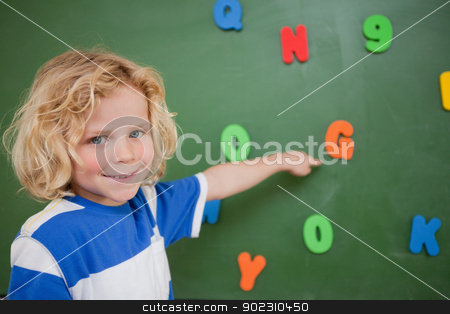 Schoolboy pointing at a letter stock photo, Schoolboy pointing at a letter on a blackboard by Wavebreak Media