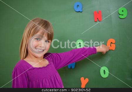 Little schoolgirl pointing at a letter stock photo, Little schoolgirl pointing at a letter in a classroom by Wavebreak Media