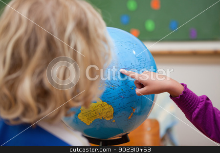 Finger of a little girl showing a country to a classmate stock photo, Finger of a little girl showing a country to a classmate on a globe by Wavebreak Media
