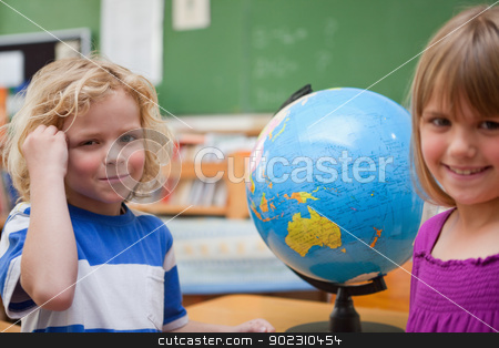 Pupils posing in front of a globe stock photo, Pupils posing in front of a globe in a classroom by Wavebreak Media