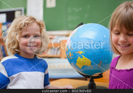 Young pupils posing in front of a globe stock photo, Young pupils posing in front of a globe in a classroom by Wavebreak Media