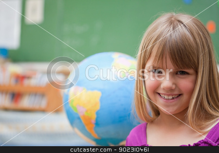 Schoolgirl posing in front of a globe stock photo, Schoolgirl posing in front of a globe in a classroom by Wavebreak Media