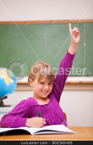 Portrait of a schoolgirl raising her hand stock photo, Portrait of a schoolgirl raising her hand in a classroom by Wavebreak Media