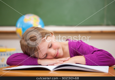 Schoolgirl sleeping on her desk stock photo, Schoolgirl sleeping on her desk in a classroom by Wavebreak Media