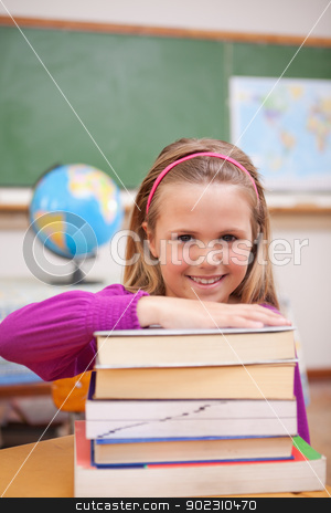 Portrait of schoolgirl posing with books stock photo, Portrait of schoolgirl posing with books in a classroom by Wavebreak Media