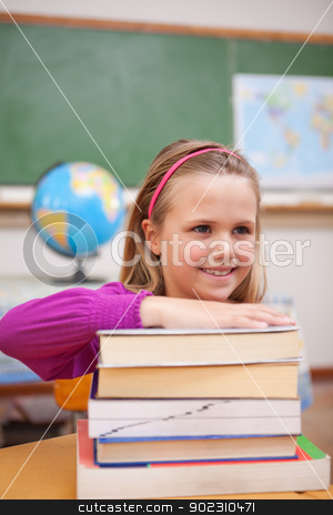Portrait of schoolgirl posing with a stack of books stock photo, Portrait of schoolgirl posing with a stack of books in a classroom by Wavebreak Media