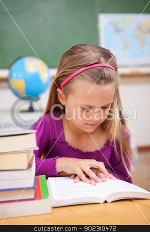 Portrait of schoolgirl reading a book stock photo, Portrait of schoolgirl reading a book in a classroom by Wavebreak Media