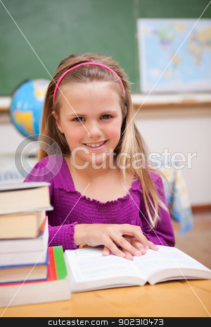 Portrait of young schoolgirl reading a book stock photo, Portrait of young schoolgirl reading a book in a classroom by Wavebreak Media