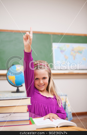 Portrait of young schoolgirl raising her hand stock photo, Portrait of young schoolgirl raising her hand in a classroom by Wavebreak Media