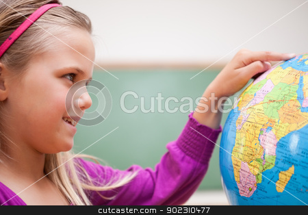 Close up of a cute schoolgirl looking at a globe stock photo, Close up of a cute schoolgirl looking at a globe in a classroom by Wavebreak Media