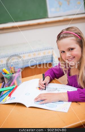 Portrait of a schoolgirl drawing stock photo, Portrait of a schoolgirl drawing in a classroom by Wavebreak Media