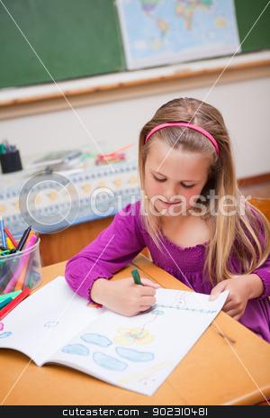 Portrait of a cute schoolgirl drawing stock photo, Portrait of a cute schoolgirl drawing in a classroom by Wavebreak Media