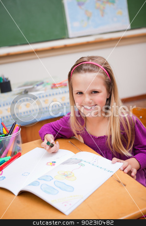 Portrait of a smiling schoolgirl drawing stock photo, Portrait of a smiling schoolgirl drawing in a classroom by Wavebreak Media