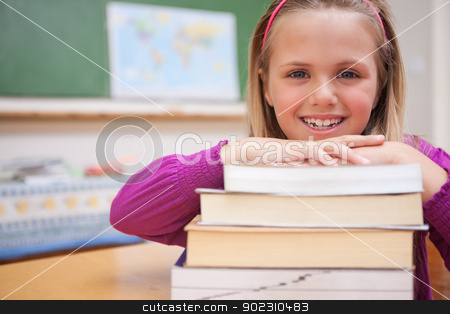 Schoolgirl posing with a stack of books stock photo, Schoolgirl posing with a stack of books in a classroom by Wavebreak Media