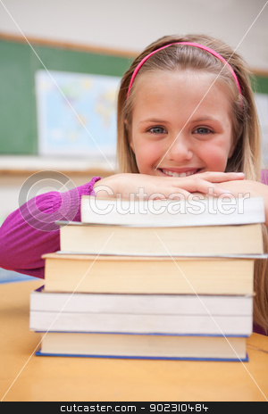 Portrait of a smiling schoolgirl posing with a stack of books stock photo, Portrait of a smiling schoolgirl posing with a stack of books in a classroom by Wavebreak Media