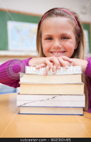 Portrait of a happy schoolgirl posing with a stack of books stock photo, Portrait of a happy schoolgirl posing with a stack of books in a classroom by Wavebreak Media
