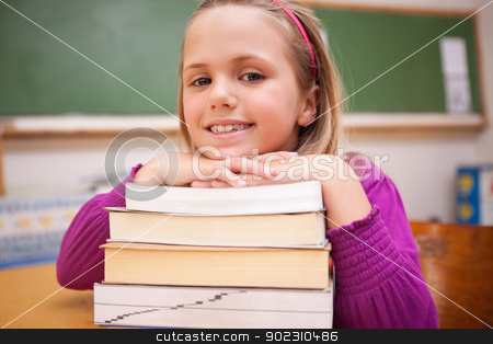 Happy schoolgirl posing with a stack of books stock photo, Happy schoolgirl posing with a stack of books in a classroom by Wavebreak Media