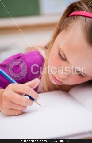 Portrait of a young schoolgirl writing stock photo, Portrait of a young schoolgirl writing in a classroom by Wavebreak Media