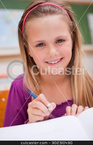 Portrait of a little schoolgirl writing stock photo, Portrait of a little schoolgirl writing in a classroom by Wavebreak Media