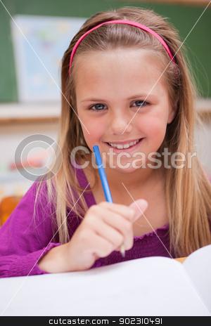 Portrait of a little schoolgirl writing on a book stock photo, Portrait of a little schoolgirl writing on a book in a classroom by Wavebreak Media