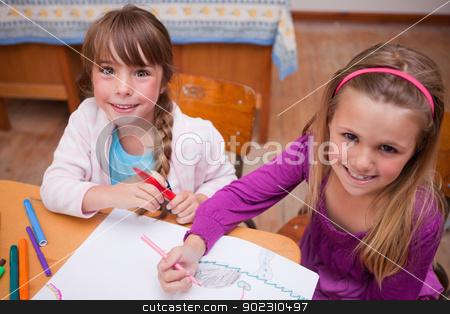 Cute schoolgirls drawing in a coloring book stock photo, Cute schoolgirls drawing in a coloring book in a classroom by Wavebreak Media