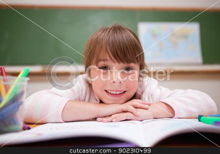 Happy schoolgirl leaning on a desk stock photo, Happy schoolgirl leaning on a desk in classroom by Wavebreak Media