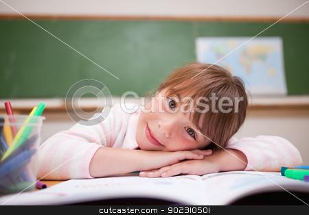 Cute schoolgirl leaning on a desk stock photo, Cute schoolgirl leaning on a desk in a classroom by Wavebreak Media