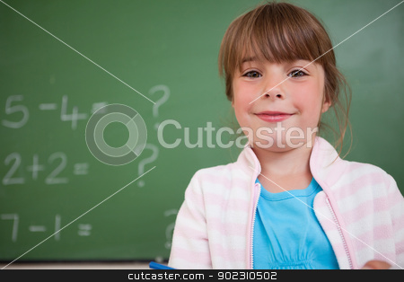 Little girl standing up stock photo, Little girl standing up in front of a blackboard by Wavebreak Media