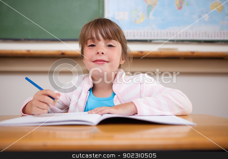 Cute girl writing stock photo, Cute girl writing in a classroom by Wavebreak Media