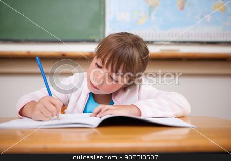 Focused girl writing stock photo, Focused girl writing in a classroom by Wavebreak Media
