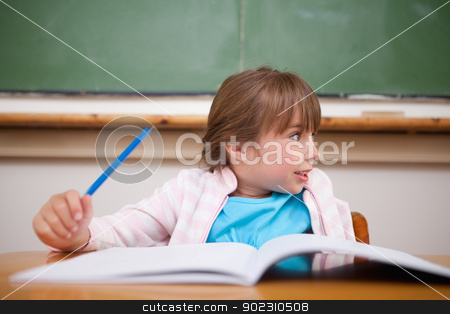 Happy girl holding a pen stock photo, Happy girl holding a pen in a classroom by Wavebreak Media