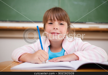 Happy girl writing stock photo, Happy girl writing in a classroom by Wavebreak Media