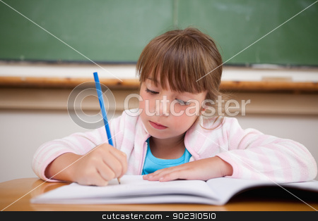 Serious girl writing stock photo, Serious girl writing in a classroom by Wavebreak Media