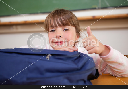 Cute schoolgirl posing with a bag and the thumb up stock photo, Cute schoolgirl posing with a bag and the thumb up in a classroom by Wavebreak Media